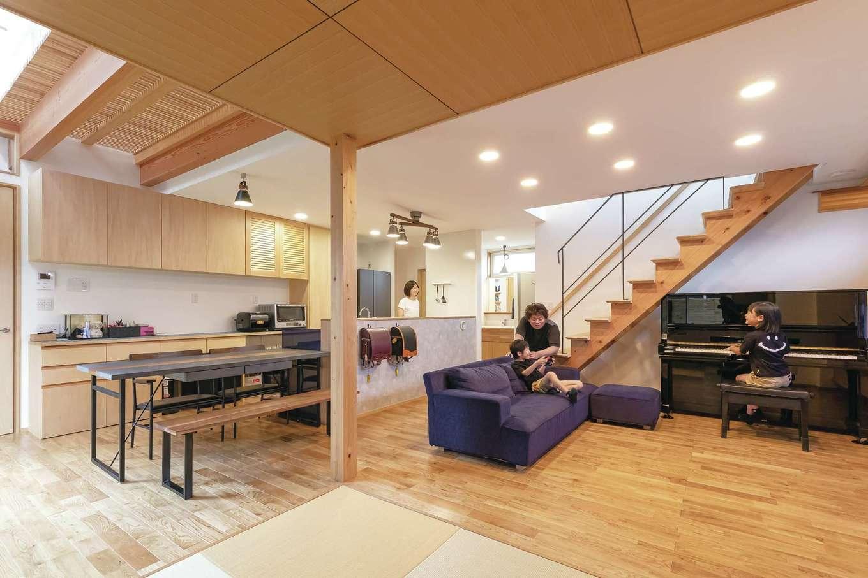 T-style ティースタイル【デザイン住宅、子育て、自然素材】つながりを持たせながらも、緩やかにゾーニングされたLDK。家族の様子を見渡せる位置にキッチンを配置した。隣接する畳コーナーには、雛人形と五月人形を飾る。板張りの天井がアクセントに。階段下のデッドスペースを活かしてピアノを置いた