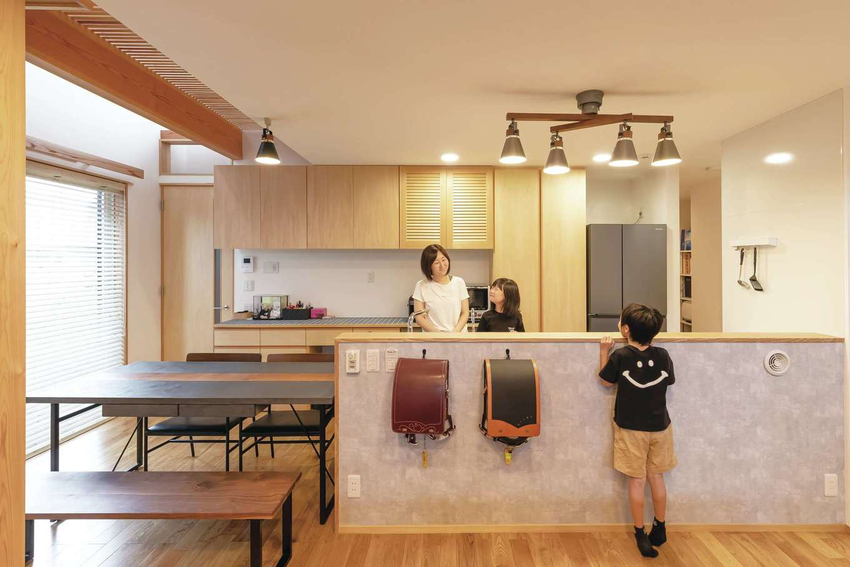 T-style ティースタイル【デザイン住宅、子育て、自然素材】北向きにレイアウトされたダイニングキッチン。ご主人も料理をするので、ワークトップは高めに。子どもたちは2階の個室ではなく、ダイニングで宿題をするため、学習用具をすぐ取り出せる位置にランドセル掛けを用意。テーブルは外壁材で造った『T-style』のオリジナル