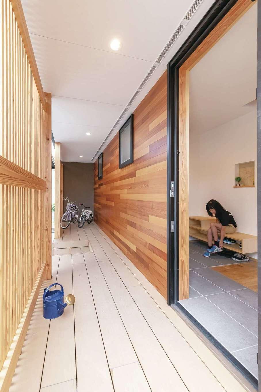 T-style ティースタイル【デザイン住宅、子育て、自然素材】屋根付きの長いポーチは、雨の日もストレスフリー。格子塀で通りからの目線をさり気なくかわせる