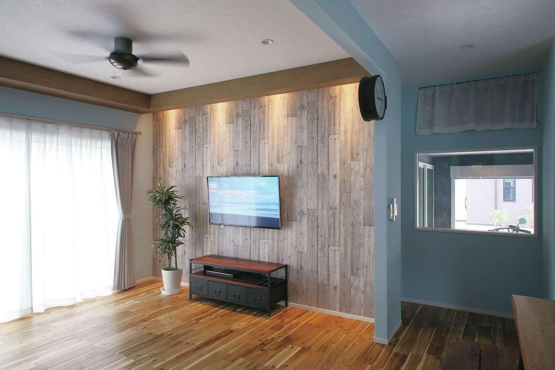 丸昇彦坂建設【デザイン住宅、趣味、間取り】アカシアの無垢フローリングと木目調の壁が印象的。室内窓の向こうにはガレージがある