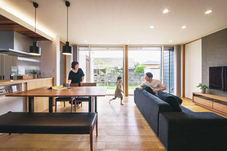 神谷綜合建設 カミヤの家【デザイン住宅、子育て、間取り】庭の景色を楽しめるよう天井まで届く大きな窓を採用。たっぷりの光が差し込み、ウッドデッキ越しに緑の庭を一望する開放感あるLDKが誕生した。レッドシダーをあしらったキッチンの天井をあえて低くすることで、視覚的にもリビングの広がりを感じられるデザイン。キッチンカウンター下には引き戸を使った収納を用意。子どもたちの絵本などをしまって、リビングはいつでもすっきり。一部にニッチを設け、カメラが趣味のご主人が撮影した家族写真をディスプレイ