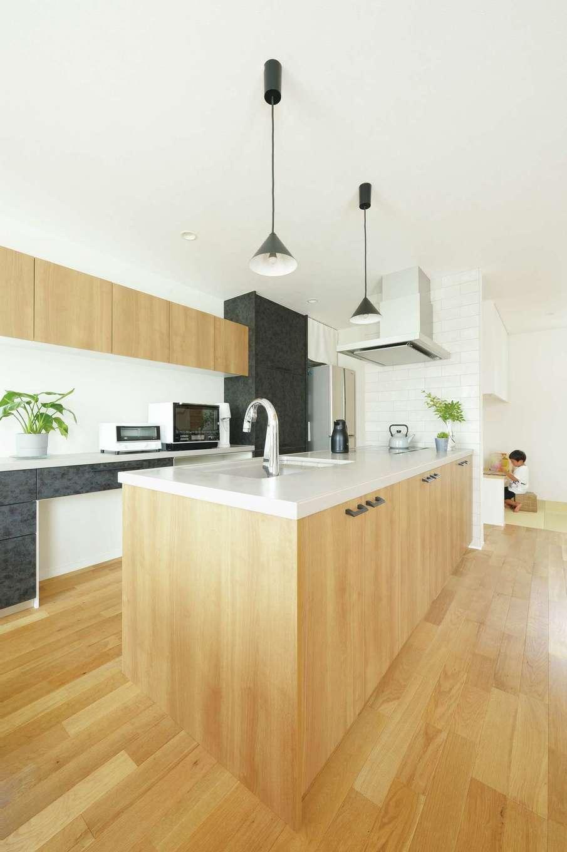 幹工務店【デザイン住宅、省エネ、間取り】木目調の扉材やグレーの人工大理石など、素材の質感や色合いにこだわったアイランドキッチン。クロスともベストマッチなキッチンスペースは、奥さまの1番の自信作