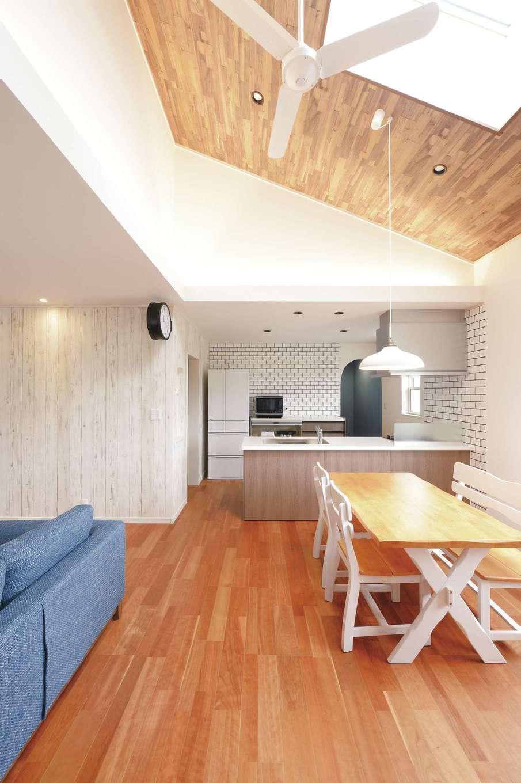 朝日住宅【デザイン住宅、間取り、平屋】L字型のLDKは、勾配天井の木目調クロスや天窓がインテリアの一部に。アーチ型開口はパントリーへつながっている