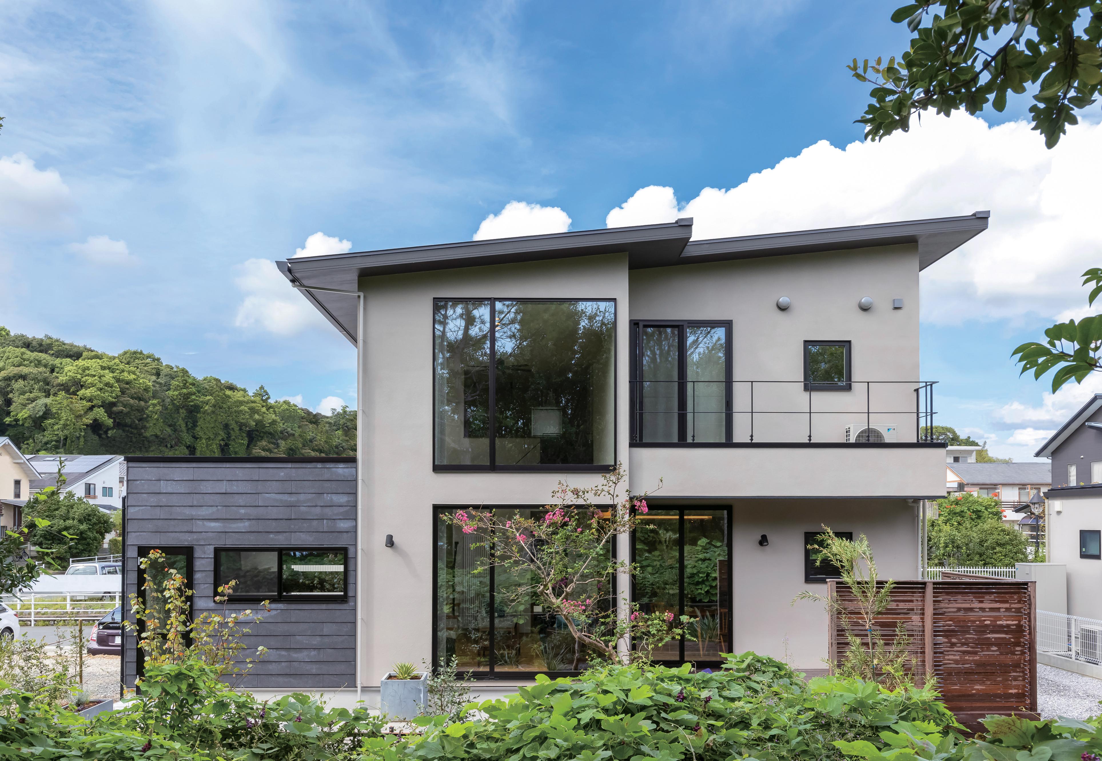 ココハウス【浜松市中区富塚町5212-7・モデルハウス】グレーの外壁に佐鳴湖畔の緑が映えるシンプルな外観。大きな窓から取り込む日の光により、室内はいつでも明るい。鉄黒色の壁がアクセント