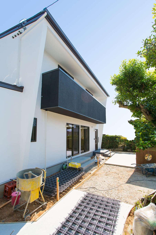 アトリエプラス【子育て、自然素材、間取り】建物の外壁も漆喰塗り。青空と緑の木々を背景に白さが際立って見える