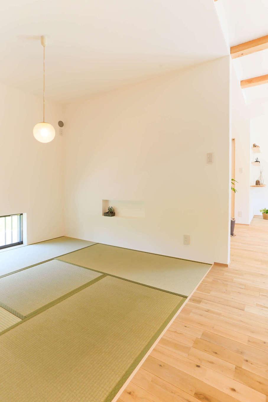 アトリエプラス【子育て、自然素材、間取り】階段の横に設けた畳コーナー。漆喰壁にニッチを設け、地窓で明るさを確保。LDKとの調和を考えてデザインされた空間が清々しさを感じさせる。子どものお昼寝やおもちゃ遊び、ゲストルームなど、多彩な過ごし方を楽しめる