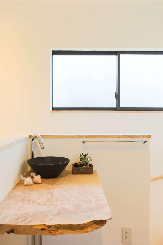 アトリエプラス【子育て、自然素材、間取り】2階の階段の脇に設けた手洗いスペース。無垢のカウンターは、夫妻がスタッフと一緒に製材屋さんに行って選んだもの。黒い陶器の手洗いボウルともベストマッチ