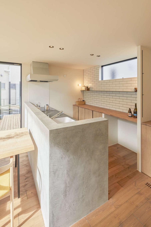 アトリエプラス【デザイン住宅、自然素材、間取り】対面キッチンはモルタルの壁でスタイリッシュに演出。リビングダイニングから作業の手元が隠れるように配慮されている。背面の造作カウンターやタイルともぴったりマッチ