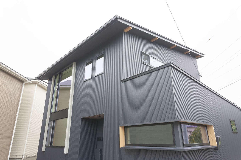 アトリエプラス【デザイン住宅、自然素材、間取り】濃いグレーで統一した外観。吹抜けの大窓やL字型の窓がアクセントとなり、クールな印象に仕上がった