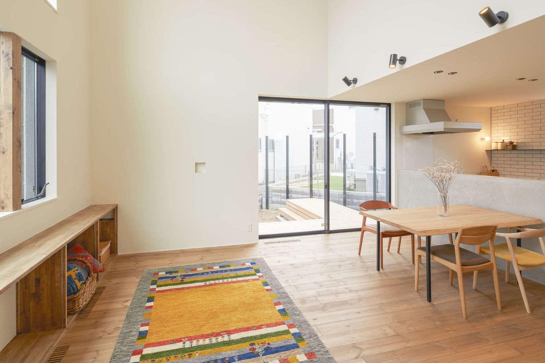 アトリエプラス【デザイン住宅、自然素材、間取り】吹き抜けのリビングとダイニングキッチンは天井高に差をつけてさりげなくゾーニング。リビングには壁に沿って造作棚を設けてあり、子どものおもちゃや生活用品を使いたいときにサッと取り出せる