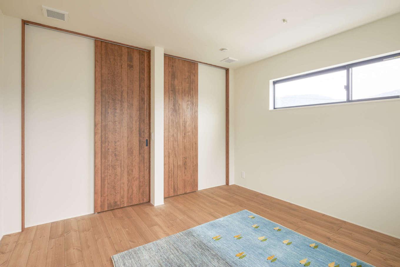 アトリエプラス【デザイン住宅、自然素材、間取り】2階の子ども部屋。室内のドアはすべて天井いっぱいまでの高さのハイドアを採用し、空間を開放的かつスタイリッシュに演出。無垢材なので、家族の健康にやさしい空間が実現