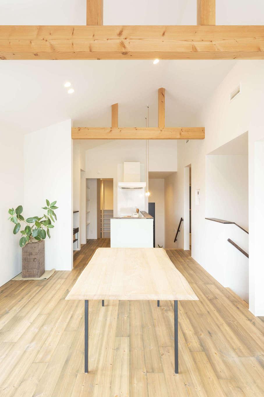 スキップフロアのダイニングキッチン。パインの無垢の床の足触りが心地よい。高天井に掛かった化粧梁がナチュラルモダンな空間を引き立てている