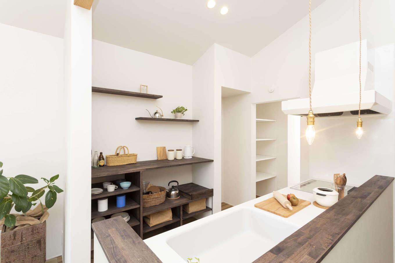 対面キッチンの背面は、オープンラックを設けて「見せる収納」を楽しむスペースに。キッチンの奥にはパントリーもあり、ストック食品やキッチン道具をまとめて収納