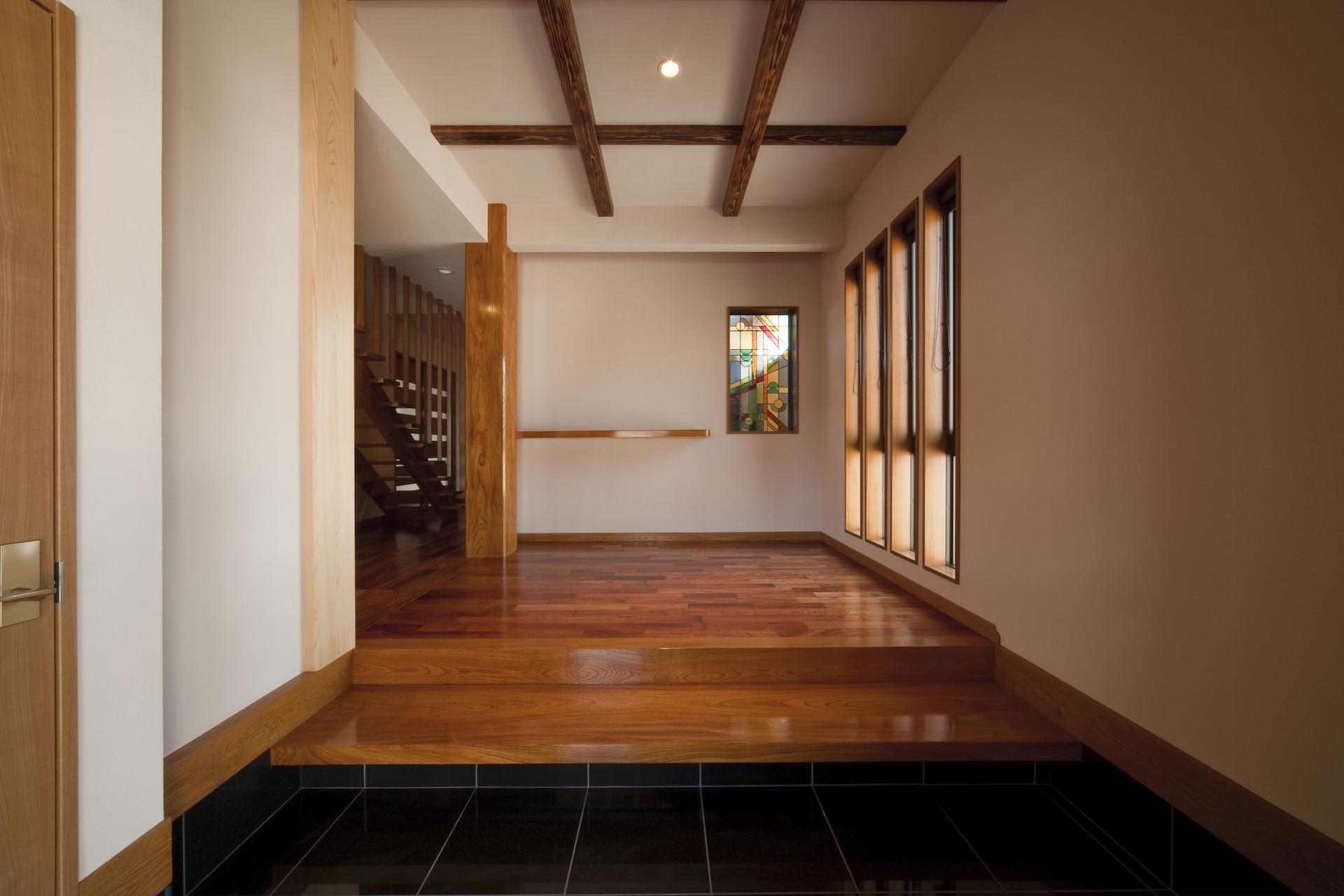 匠集団 槌音(つちおと)【デザイン住宅、和風、二世帯住宅】正面に欅の大黒柱を配した玄関。奥さまお気に入りのステンドグラスが空間に彩りを添える