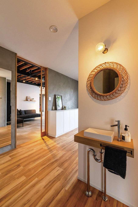 ナチュラルシックな雰囲気の玄関。トイレが直接見えないよう壁を設け、背後に来客用の手洗いを用意