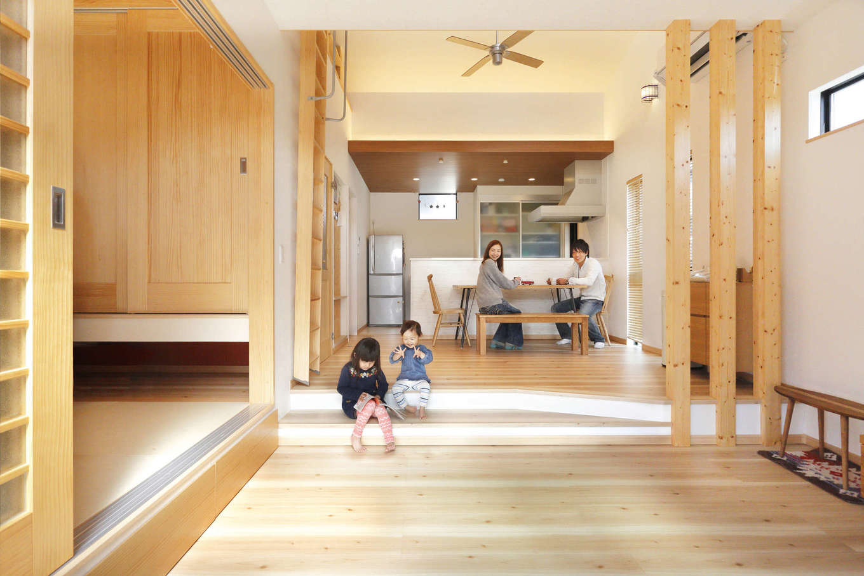 吉川住建【収納力、間取り、平屋】LDKと和室を合わせて24.4畳の大空間。リビングを一段下げたことで空間に変化が生まれ、快適に過ごすことができる。奥さまはキッチンから和室まで目が届くので、子どもを遊ばせておきながら料理ができる