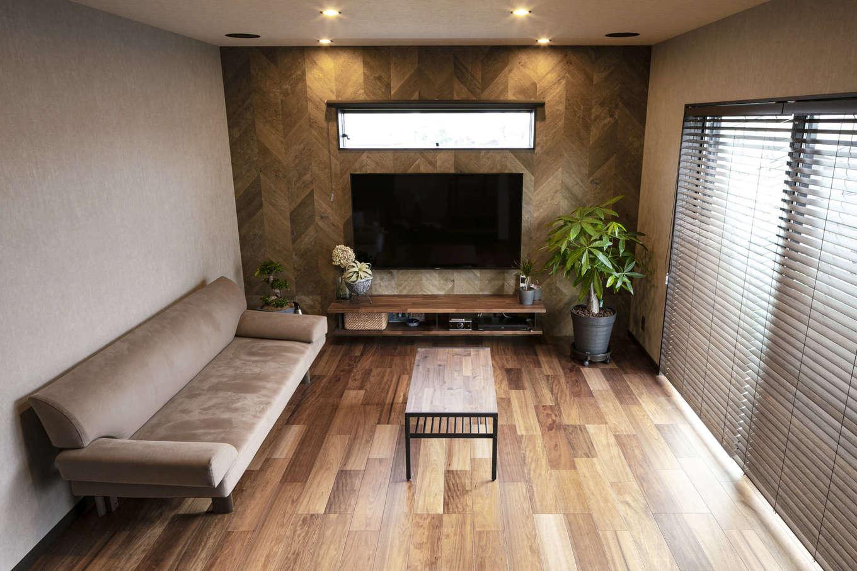 吉川住建【デザイン住宅、屋上バルコニー、ガレージ】1階のリビング。TVボードの壁一面にヘリンボーンをあしらった3ミリ厚の木質パネルを貼ってニュアンスを出した