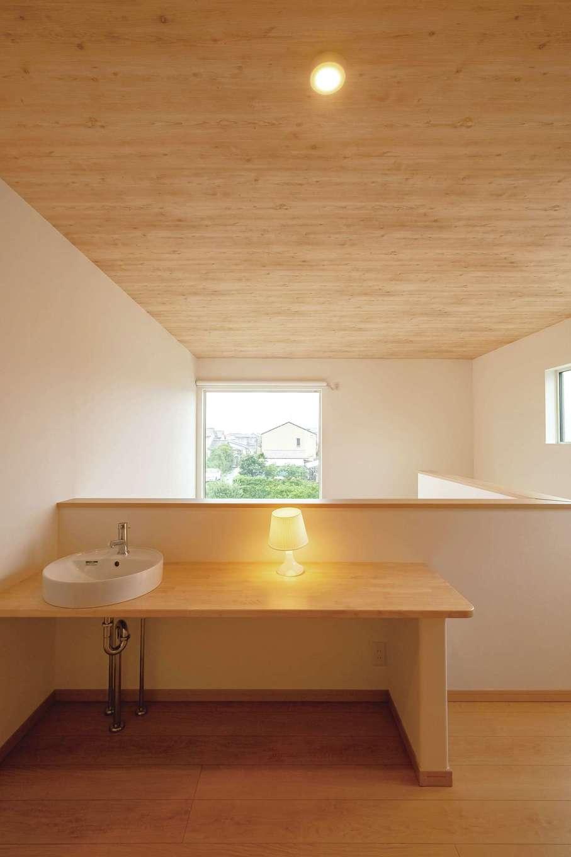 2階フリースペース。カウンターの先に見えるFIX窓が緑の風景を切り取ってくれる。吹抜けの天井に木目調のクロスを貼ったことで、家全体が木のぬくもりに満ちたナチュラルな雰囲気になった
