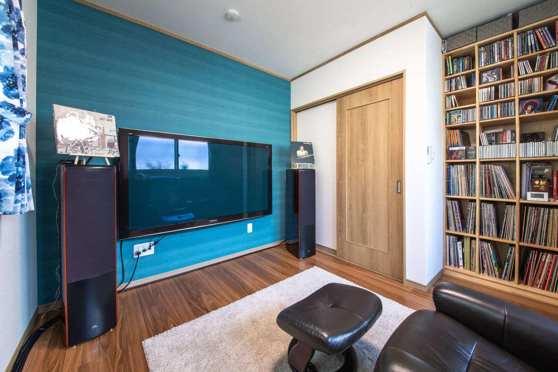 有無ホーム【夫婦で暮らす、間取り、平屋】ご主人の趣味の書斎は、濃いブルーのアクセントクロスが映える空間。造作の収納棚には、お気に入りのLPレコードやCDがぎっしりと並ぶ。高気密・高断熱で防音性も高いうえに、内窓を設けたことで、周囲への音漏れを気にせず、音楽鑑賞を楽しめる