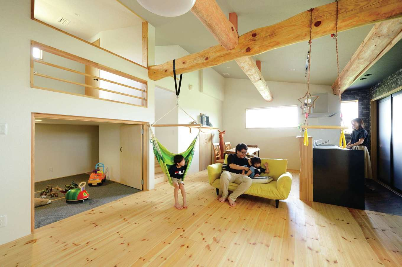 アキケンチク【デザイン住宅、二世帯住宅、自然素材】2階子世帯のLDKは23畳の大空間。勾配天井を交差する野物の梁がアクセントになっている。スキップフロアの下はご主人の趣味部屋、上は子ども部屋になる予定
