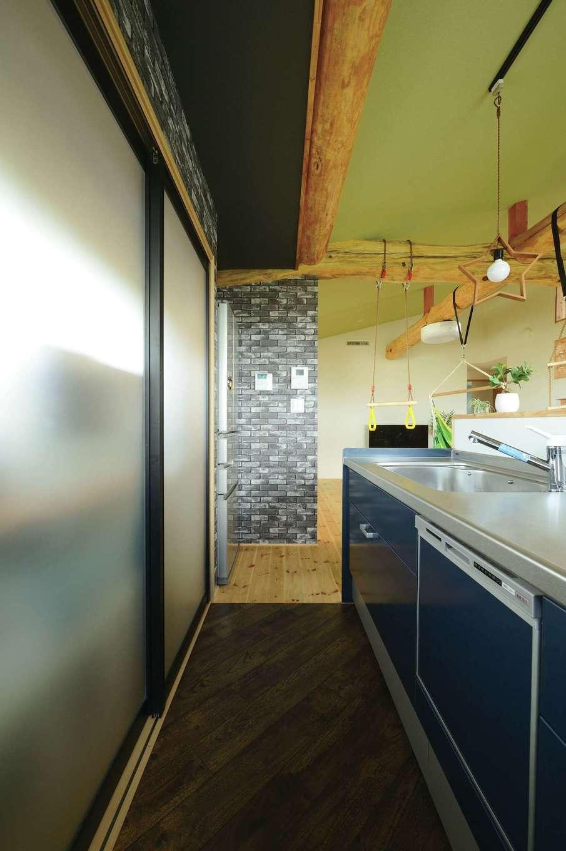 アキケンチク【デザイン住宅、二世帯住宅、自然素材】家族の様子を見渡せる場所にキッチンを配置。不意の来客時でも食器棚をサッと隠せるよう半透明の引き戸を採用。引き戸の奥はガラス張りで光も取り込める
