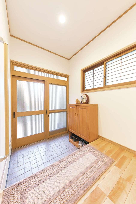 サラサホーム沼津(靖和工務店)|玄関の開口部とたたきはそのまま活用。フローリングの色と合わせて、既存サッシの窓枠には新たな木枠を取り付けて統一感を持たせた