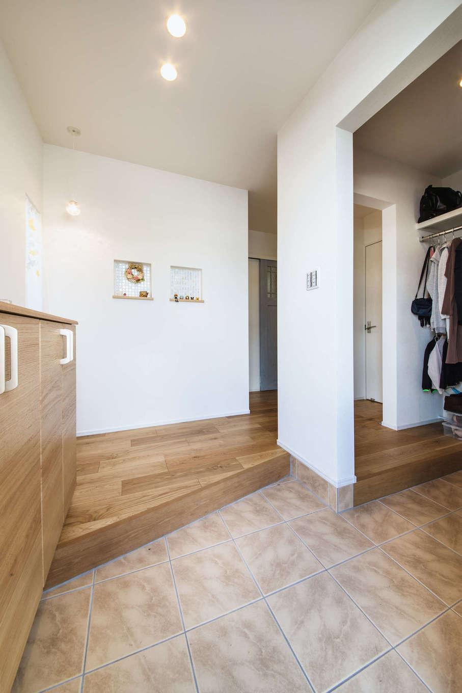 アルファホーム【収納力、省エネ、間取り】ゆったりとした玄関ホール。タイル貼りの可愛らしいニッチ、お気に入りのペンダントライトを採用し、ディスプレイも楽しめる。2畳の土間収納には外着もかけられるハンガーパイプを設置した