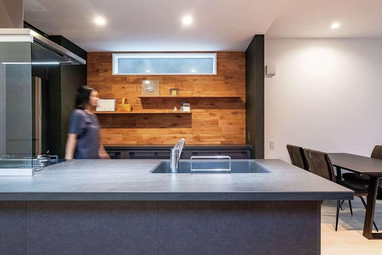 ハートホーム【デザイン住宅、二世帯住宅、間取り】セラミック天板のキッチンはそれ自体がインテリアのよう。木を使う範囲は周囲とのバランスを考え背面のみに。家電は隣接するパントリーに収め、すっきり整った状態を保てる