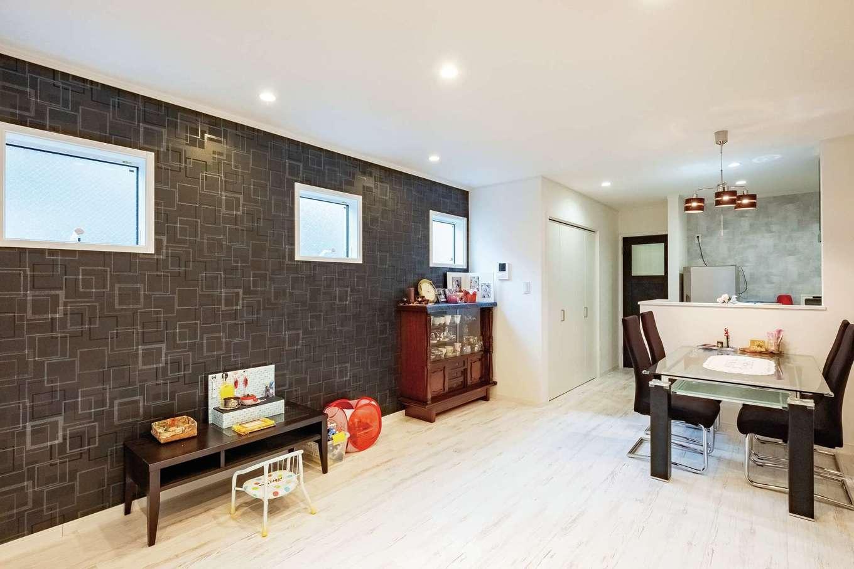 ハートホーム【デザイン住宅、二世帯住宅、間取り】お母さまが暮らす1階LDKは対面キッチンのコンパクトな造り。3つ並んだ窓からたっぷりの光が入る。白ベースの空間も部屋を明るくする工夫の一つだ