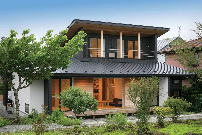TENアーキテクツ 一級建築士事務所【デザイン住宅、和風、建築家】ガルバ、塗り壁、無垢をバランスよく組み合わせ、個性と落ち着きが調和する外観に。庭とその先の畑に面した南面は開口部を大きく取り、光や風とともに敷地の魅力を室内に招いている。「内部の掃除がしにくい戸袋は設置したくなくて」という奥さまの要望を受け、木製の雨戸自体が開閉するアイデアが採用された