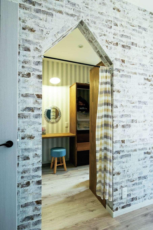 甲静ハウジング【デザイン住宅、趣味、間取り】シックな寝室はレンガ調のクロスを用いた。ウォークインクローゼットの入り口は、三角屋根のような開口部に。入るとすぐの場所にドレッサーコーナーを設置。身支度動線も便利に