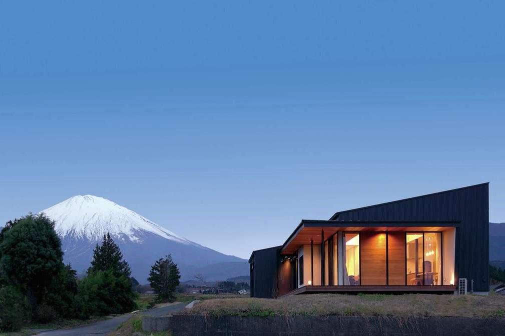 TENアーキテクツ 一級建築士事務所【デザイン住宅、建築家、平屋】富士山を間近に望むことができる好ロケーションに建つ。外観はグレーのガルバリウム鋼板に、重厚でモダンなチークの板張りがアクセント。勾配天井部分がロフトになっている