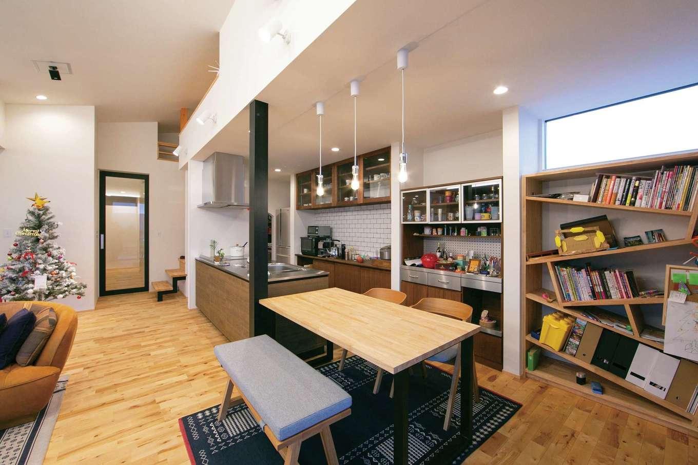TENアーキテクツ 一級建築士事務所【デザイン住宅、建築家、平屋】ハーフ吹抜けのあるLDK。ダイニングテーブルをキッチンと横並びにすることで、家事効率が高まり、空間を広く使うこともできる。斜めに板を組み合わせた造作の書棚がインテリアのワンポイントに