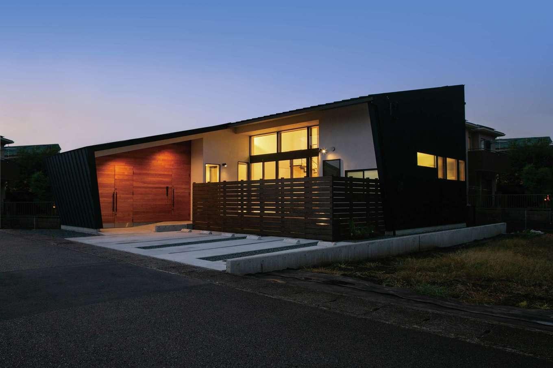 TENアーキテクツ 一級建築士事務所【デザイン住宅、間取り、建築家】一枚屋根から外壁へとつながる平屋風の外観。独創的なプロポーションは設計力に定評のある『TENアーキテクツ』ならでは。帽子のつばのように長く伸ばした軒が、夏の直射日光をカットし、冬は室内の奥まで光を招き入れる。人通りが多いため、ウッドフェンスで緩やかに視線を遮り、プライバシーを確保する