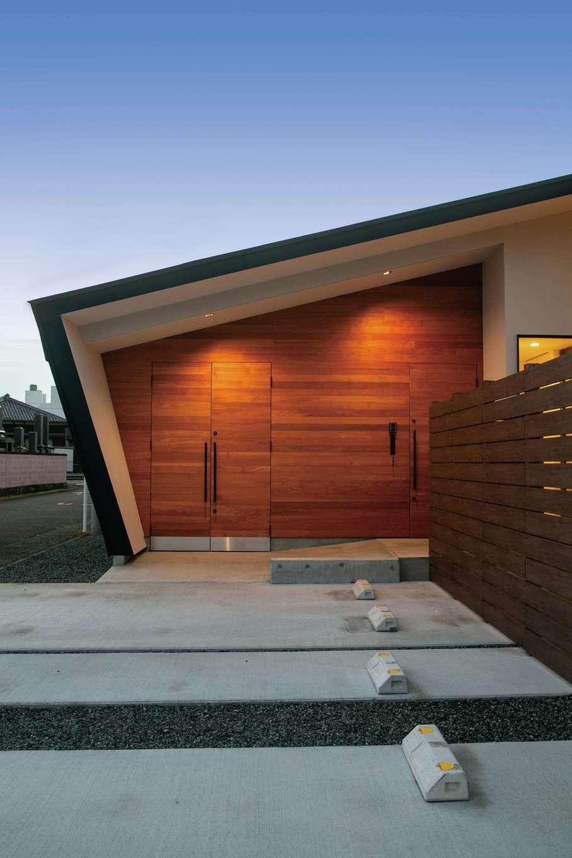 TENアーキテクツ 一級建築士事務所【デザイン住宅、間取り、建築家】レッドシダーを贅沢に使い、玄関ドアとバイクガレージの観音扉が一体化したファサード。木のぬくもりと同時に高級感が漂う建築家らしいデザイン