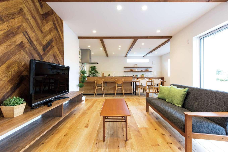KureKen 榑林建設【デザイン住宅、省エネ、間取り】無垢オークのぬくもりに包まれるリビング。ヘリンボーンの壁がアクセント。「料理中も子どもを見守りたい」という奥さまの希望を叶えたキッチンからはリビング全体の様子が見渡せる