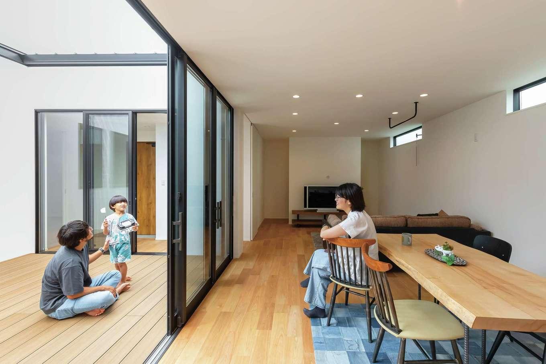 ティアラホームスタイル【デザイン住宅、子育て、平屋】天井まで届く窓が十分な光をLDKに届ける。室内は白基調で明るさアップ。黒を部分的に使いアクセントとした。テレビの後ろは耐力壁を利用した収納。まさに無駄がない