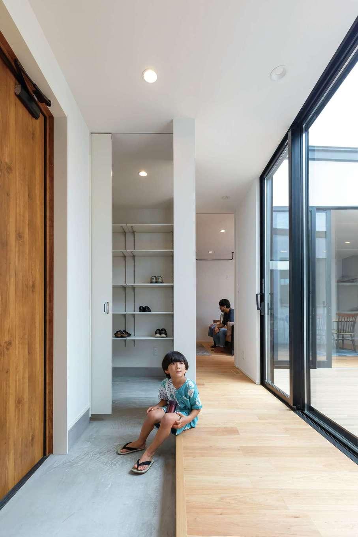 ティアラホームスタイル【デザイン住宅、子育て、平屋】目の前に広がる中庭のおかげで玄関もさんさんと明るい。扉で隠せる3畳のシューズクロークには趣味のキャンプ用品もたくさん収納できる