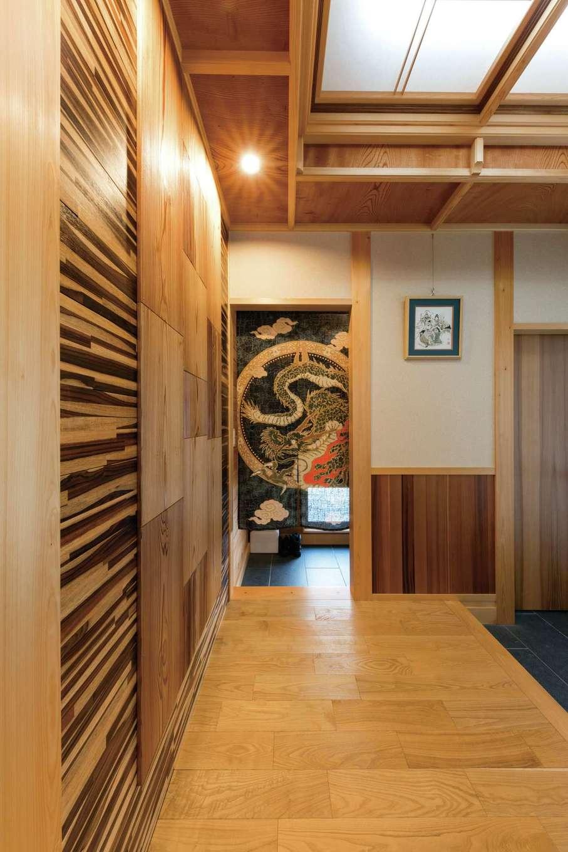 櫻 工務店【和風、自然素材、間取り】玄関ホールは、ヒノキ柱にケヤキの折り上げ天井…と木組みを現した贅沢なつくり。アーティスティックな壁は、秋田スギとローズウッドをそれぞれ特殊加工したもの