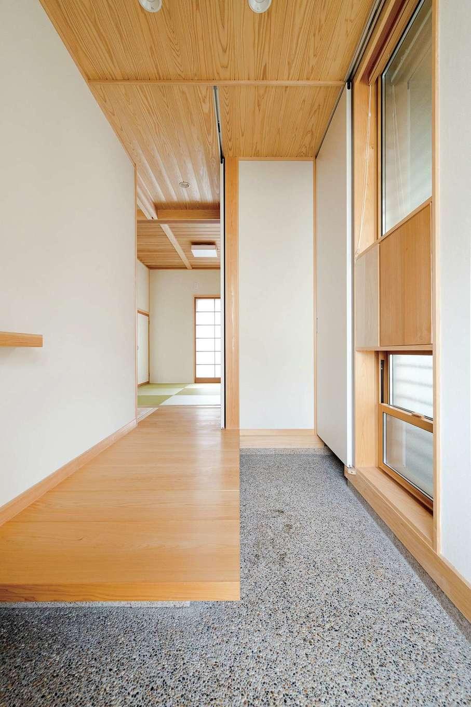 コバヤシ建築【収納力、和風、自然素材】玄関で迎えてくれるのは、55㎜と厚みのあるヒノキの床板。正面には、右手にある吊り式の引き戸と、ホールの両方から出入りできるシューズクロークが隠れている