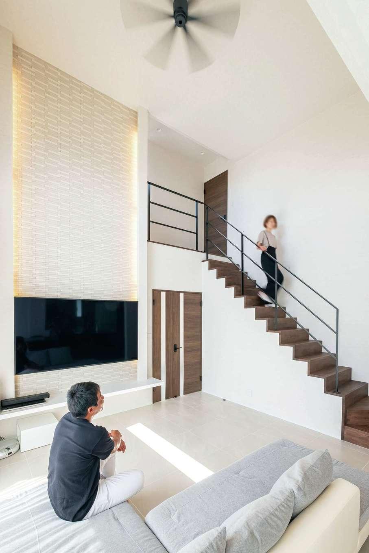 藤井建築事務所 -delphi-【デザイン住宅、建築家、インテリア】高さ5mもある吹抜けの大空間リビング。清潔感のある白で統一し、リゾートホテルのような優雅な暮らしを楽しむ。テレビの背面は調湿性にすぐれたエコカラットを贅沢に使用