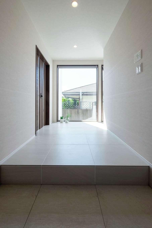 藤井建築事務所 -delphi-【デザイン住宅、建築家、インテリア】大きなFIX窓の先へと目線が抜けていく、開放感あふれる玄関ホール。600mm角のタイルを採用し、高級感のある仕上がりに