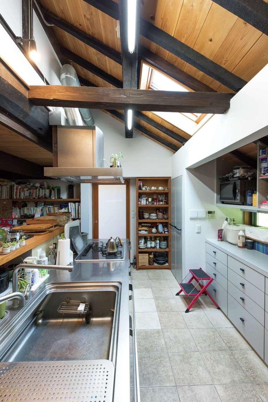 建杜 KENT(大栄工業)|勾配天井で開放感のあるキッチン。古き良き雰囲気と機能性が同居して、ぬくもりのにじむ使いやすい空間になった。カウンターの向こう側は書斎スペース。仕事を持ち帰った奥さまが、食事の支度をしながら作業を進められるベストポジションにデスク、本棚を造作
