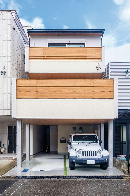 靖和工務店【子育て、狭小住宅、間取り】バルコニーの木製フェンスがナチュラルな印象の外観。張り出したバルコニーの支柱は、安心の鉄骨製で、駐車場2台分を確保。玄関脇には便利なサイクルポートを完備