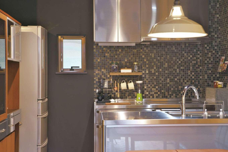 あすなろ設計事務所|キッチンは落ち着いたトーンに。ステンレスやモザイクタイルなどの素材でも、リビング部分と変化をつけている