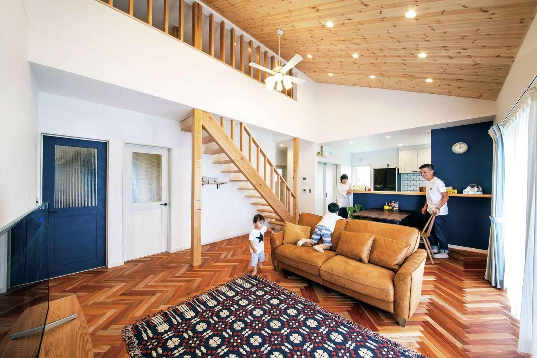水田建設【デザイン住宅、省エネ、平屋】ヘリンボーンの無垢の床が広がる本格カリフォルニアテイストのLDK。勾配天井が開放感をもたらし、ネイビーブルーのドアやキッチンが広い空間を引き締めている