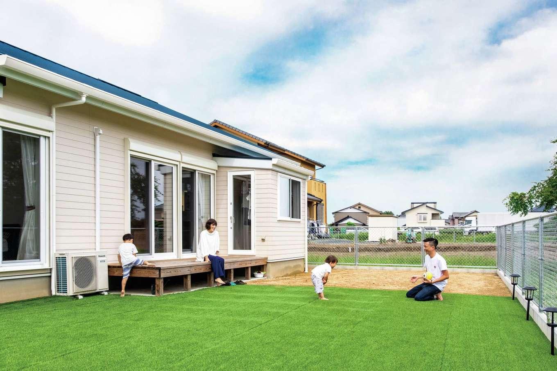 水田建設【デザイン住宅、省エネ、平屋】人工芝を敷き詰めた庭で子どもと遊ぶひととき。ウッドデッキが内と外をつなぎ、庭がいっそう身近に感じられる