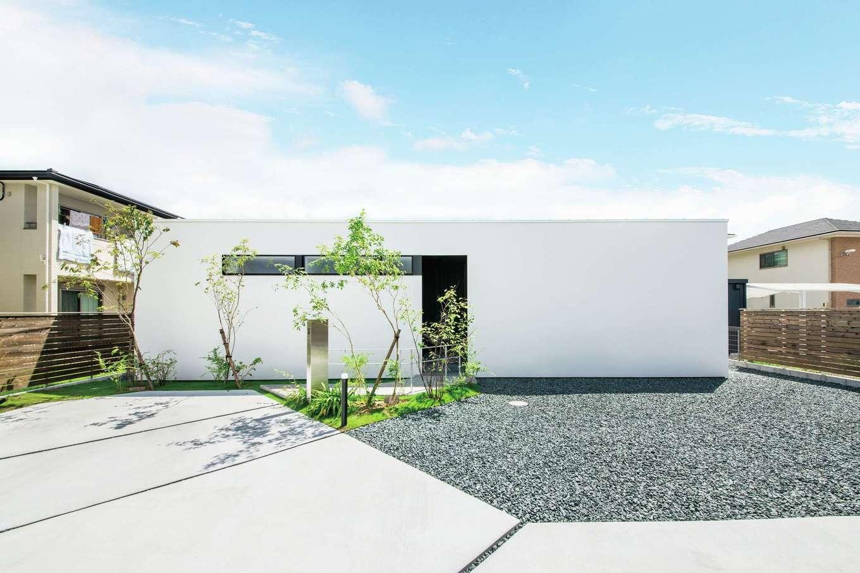 インフィルプラス【デザイン住宅、高級住宅、平屋】進入路を進むと、真っ白な箱型の外観が姿を見せる。玄関ポーチと水回りの窓の配置を工夫してL字の黒い帯のようなシェイプを形成し、ファサードにアクセントを付けた