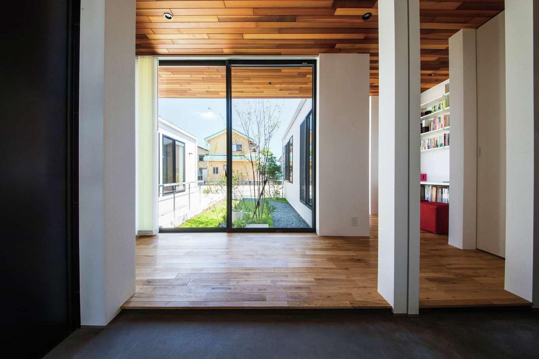 インフィルプラス【デザイン住宅、高級住宅、平屋】シューズクローク付きの玄関。モルタルの土間の正面に中庭が広がる。天井と軒天をレッドシダー張りに統一し、内が外に広がるような印象に