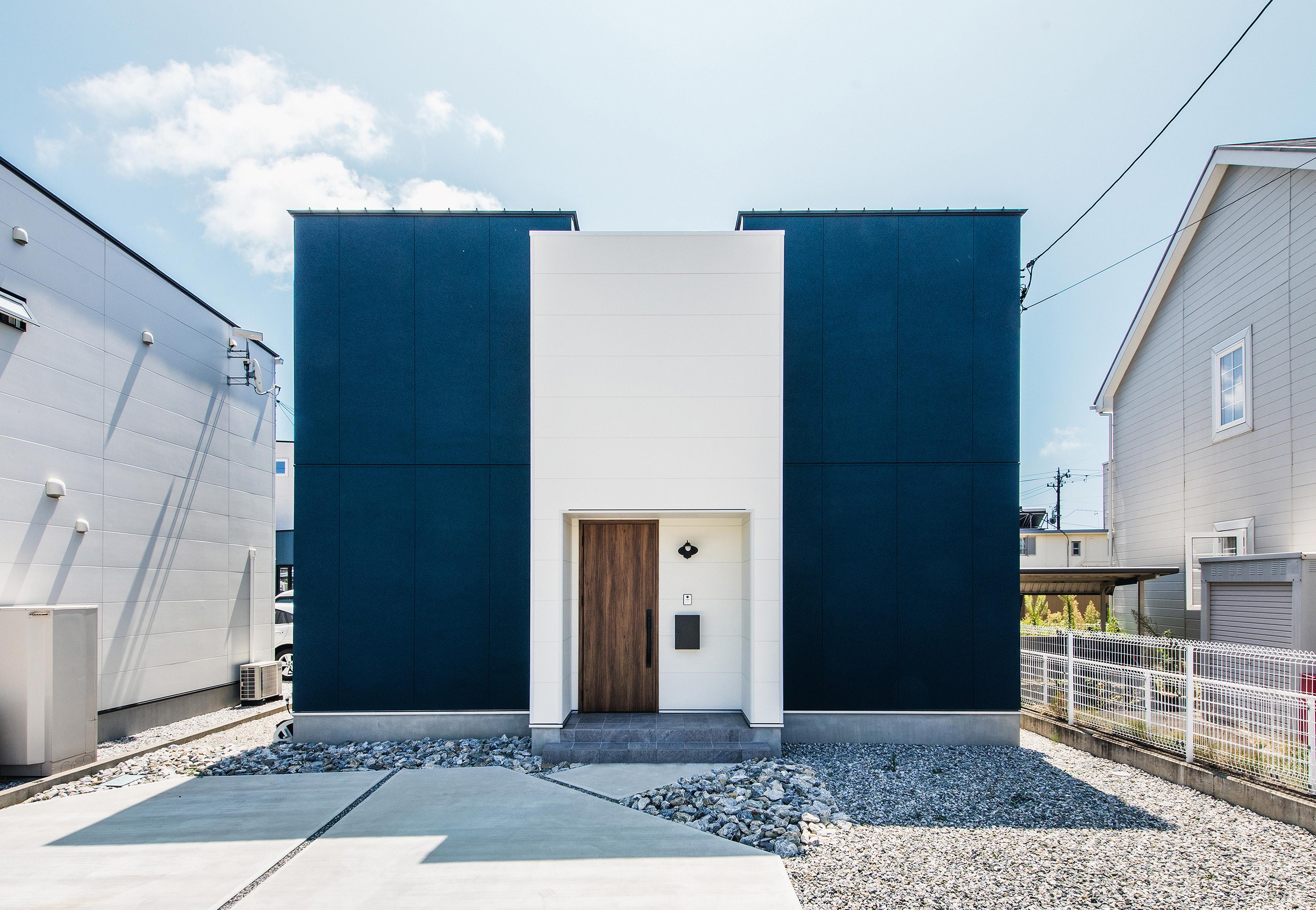 R+house 浜松中央(西遠建設)【趣味、建築家、1000万円台】白×ネイビーのコンビネーションが爽やかなキューブ型の2階建て。白い外壁の奥にバルコニーがあり、道路側の視線を遮ってプライベートなアウトドア空間を確保